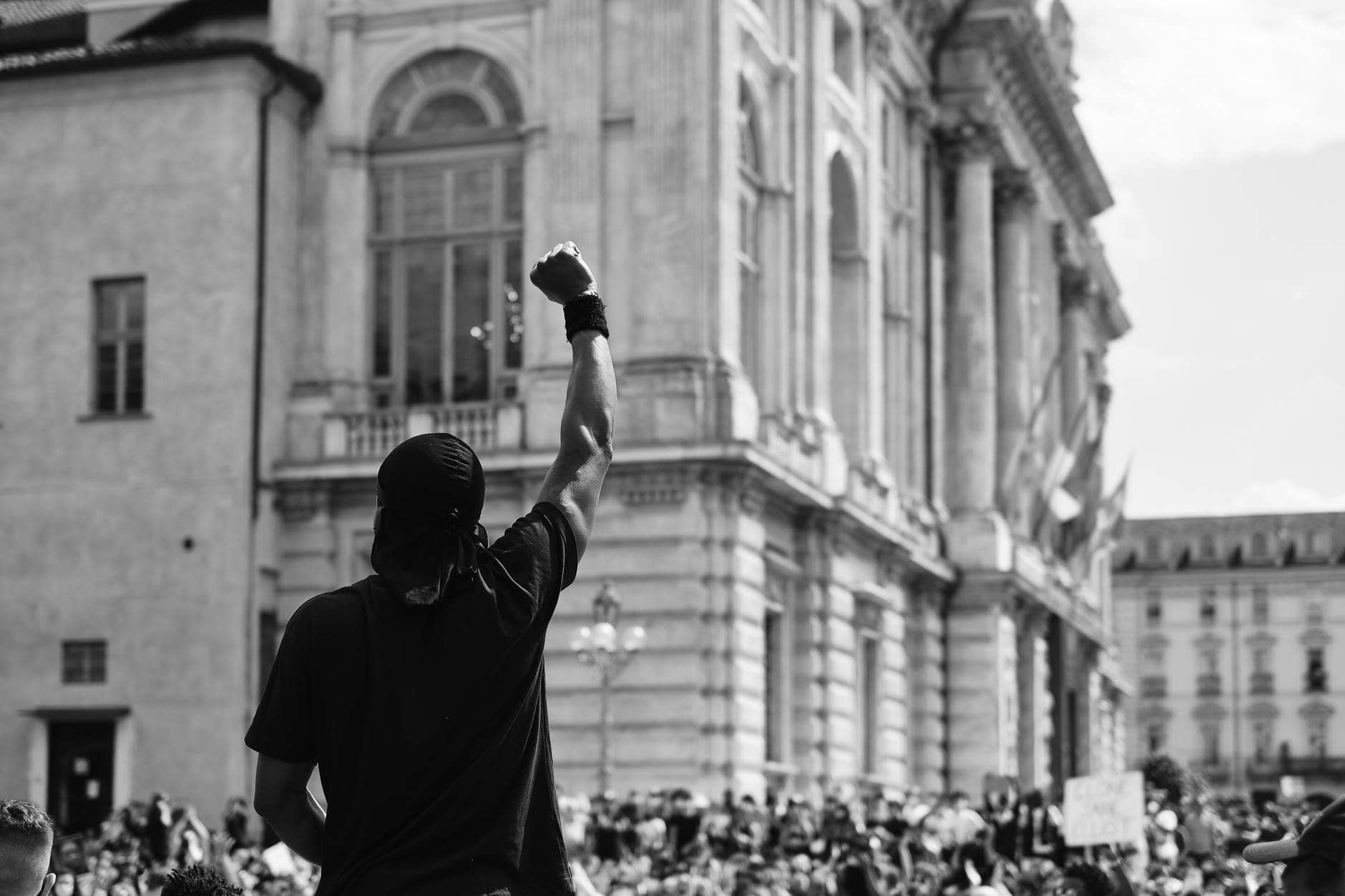 man in black t shirt standing infront of a crowd in protest
