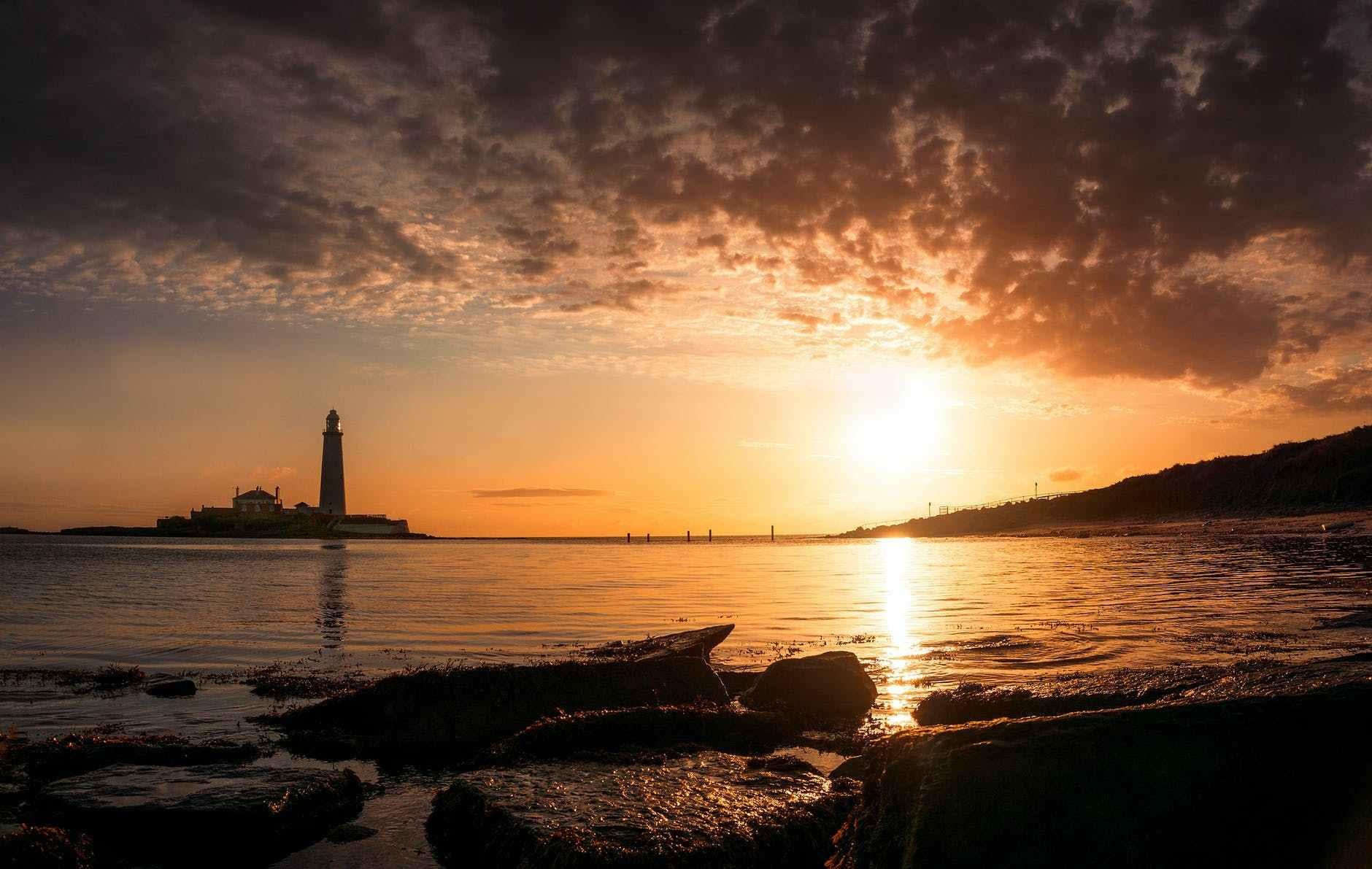 beach near island with lighthouse