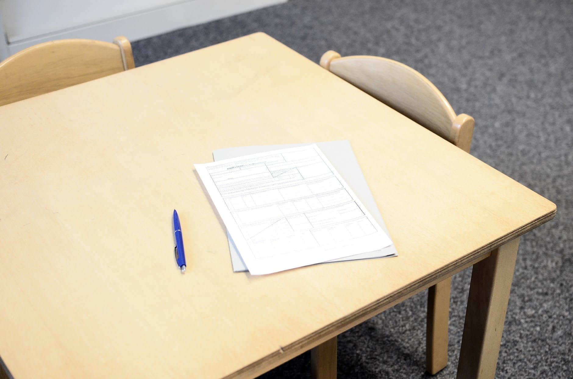 papers with pen on table in classroom